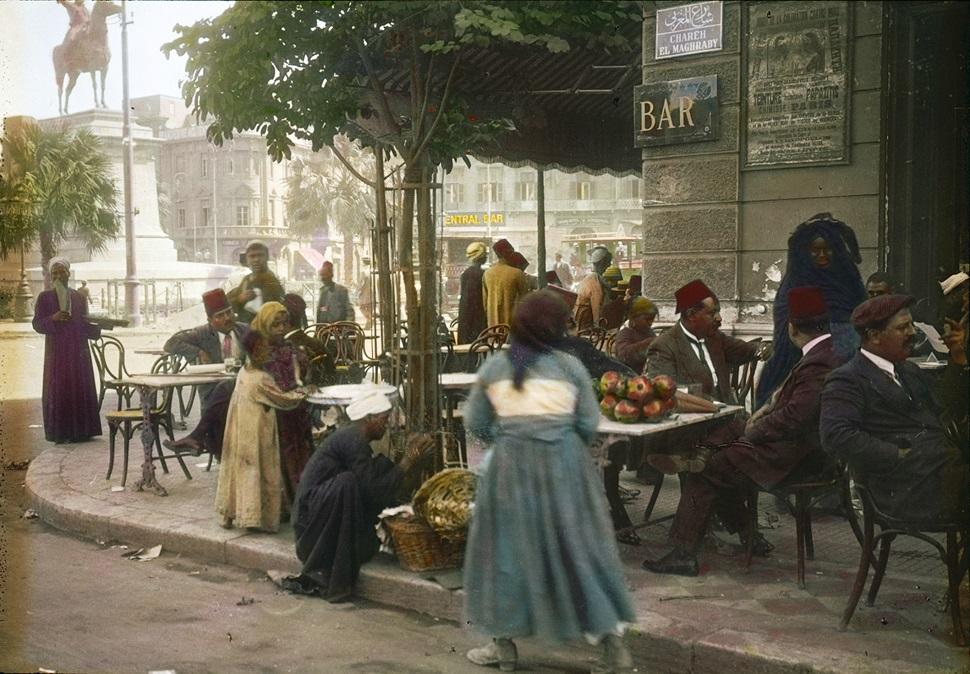 19세기 말 이집트 관광 홍보용 엽서에 사용되었던 흑백사진을 컬러화한 이미지. 이 사진은 1912년 비엔나의 관광 대행 여행사인 우라니아(Urania)의 루드비히 쾨슬러(Ludwig Koessler)가 부유층 관광객 76명을 이끌고 이집트 관광을 하던 중 수도 카이로에서 찍은 한 거리 카페의 풍경이다. © Österreichisches Volkshochschularchiv.