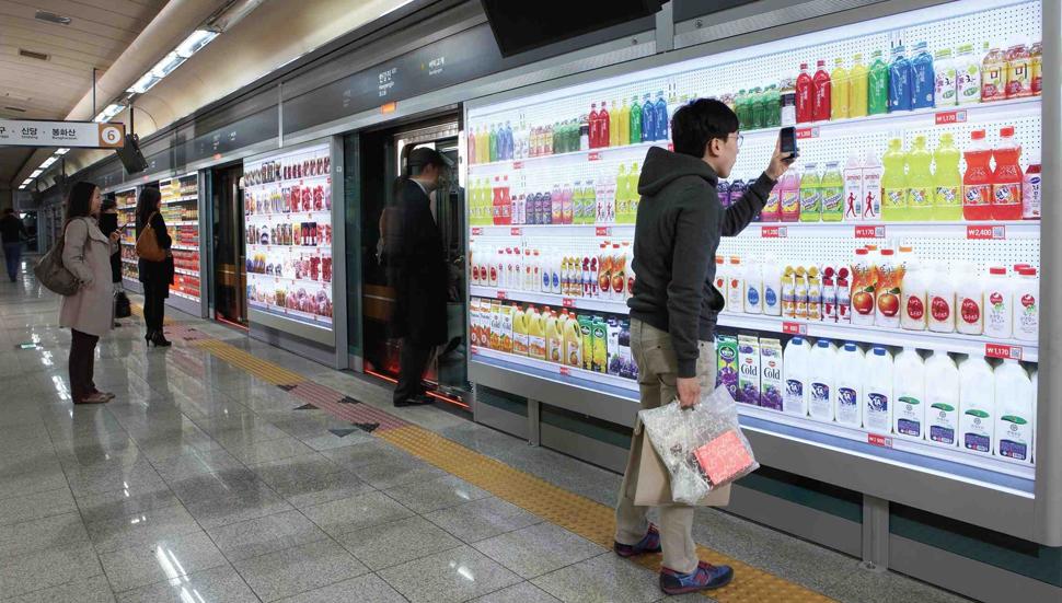 일찍이 2011년 테스코 홈플러스 슈퍼마켓 체인이 서울과 부산 지하철 역사에서 시도했던 가상 슈퍼마켓 빌보드 광고 캠페인. 스마트 기기 사용에 매우 친숙한 우리나라 소비자∙유저들은 지하철 승강장에서 전차를 기다리는 동안 스마트폰으로 관심 있는 제품의 QR코드를 스캔해 온라인 쇼핑바구니에 담은 후 결제를 하면 집에 당도했을 즈음 주문한 장바구니를 집 앞 현관에 배달받는다는 미래 장보기 가상 시나리오를 거리낌 없이 수용했다. Image courtesy: TESCO PLC.