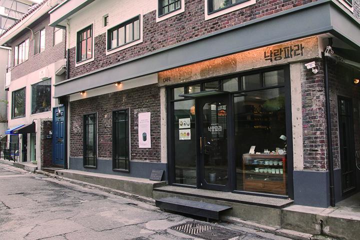 카페 입구부분 노출 콘크리트에 페인팅한 '낙랑파라' 간판은 은은한 조명을 이용해 주목성을 높였다.