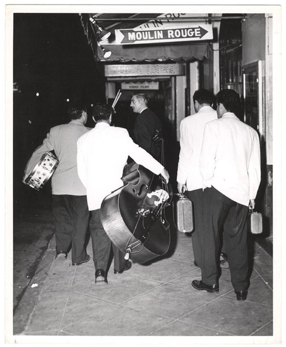 한밤중 물랭루주와 제브라 라운지라고 쓰여있는 나이트클럽 간판 아래로 음악 연주용 악기를 들고 한판의 '긱'을 하러 혹은 끝마친 후 터덜터덜 보도 위를 걸어가는 음악 밴드의 뒷모습은 미국 사진저널리스트 위지(Weegee)가 찍었다. Image Courtesy: © International Center of Photography.